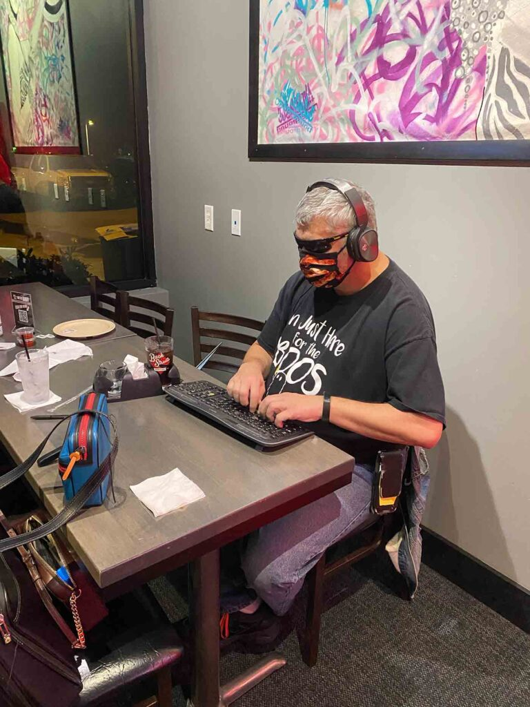 Joe at BackStreets, September 2020. He's wearing a bacon-themed mask, sunglasses and headphones as he types on a keyboard.
